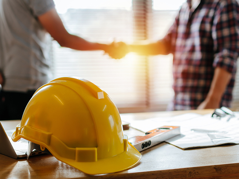 Yellow,Safety,Helmet,On,Workplace,Desk,With,Construction,Worker,Team